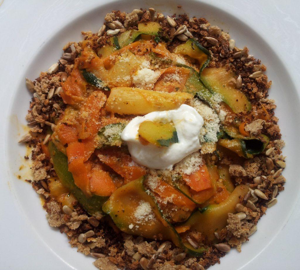 Zucchini- und Karottennudeln mit geröstetem Brotreste- und Sonnenblumenkernrand